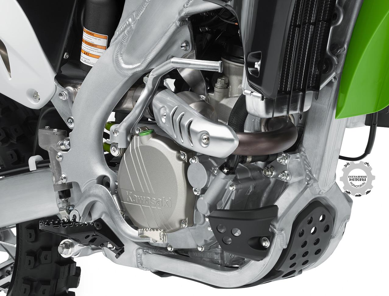 """Четырёхтактный двигатель Kawasaki KX250F 2015 сохранил прежний диаметр цилиндра и ход поршня, но получил новый поршень конструкции """"bridged box"""" а-ля Формула-1 наряду с обновлённым нижним топливным инжектором, более тяжёлым ротором раздатчика зажигания и обновлённым программированием блока управления мотором."""