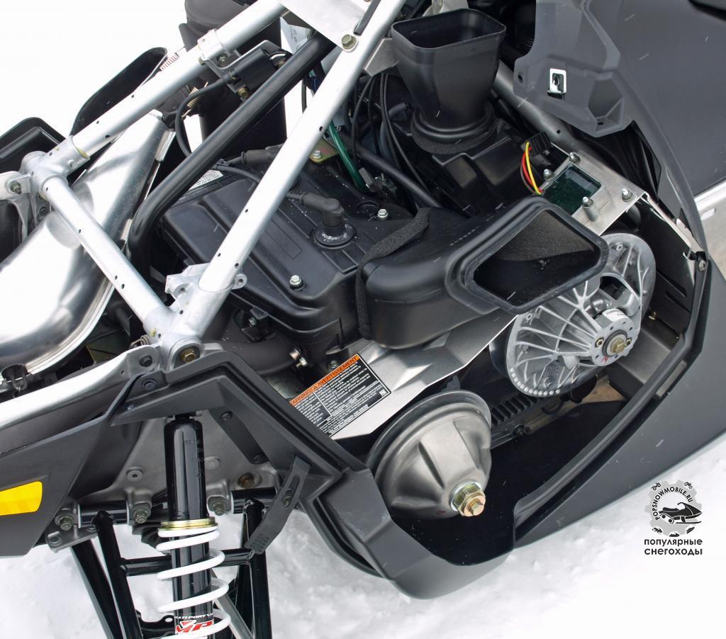 Использование 550-кубового двигателя с воздушным охлаждением потребовало множество воздуховодов и переход на сцепление от CVTech. Обратите внимание на треугольную конструкцию над двигателем, придающую снегоходу устойчивости и жёсткости.
