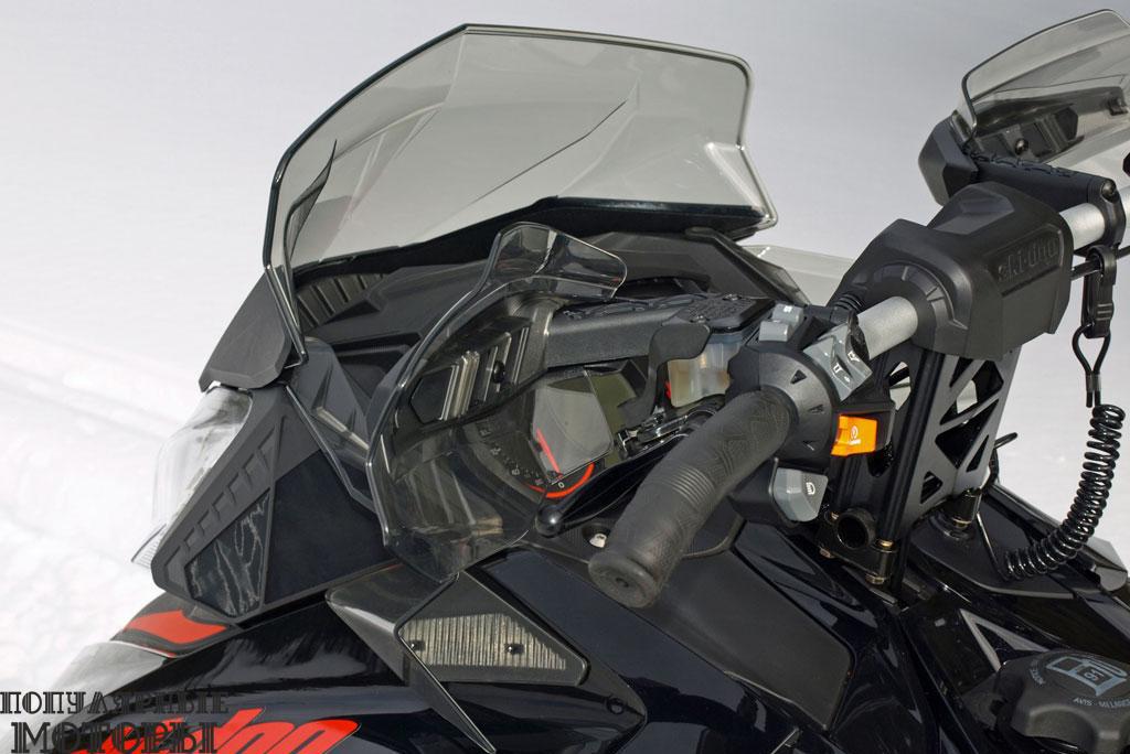 Низкое ветровое стекло — показатель высокой мощности снегохода. Ski-Doo Renegade X также оборудован прозрачными пластиковыми защитными щитками для рук и изогнутыми ручками руля.