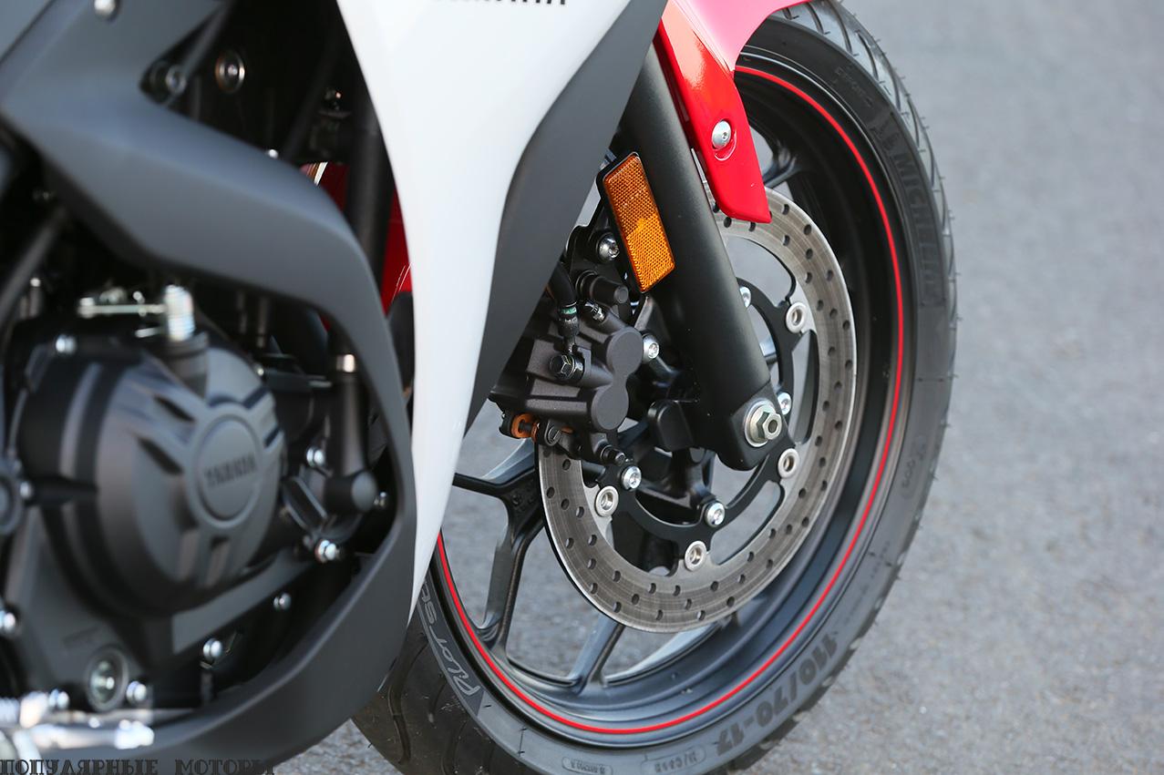 Один 298-миллиметровый тормозной диск спереди с двухпоршневым суппортом Akebono делает основную долю работы во время торможения. Также обратите внимание на 10-спицевое литое алюминиевое колесо и резину Michelin Pilot Street.